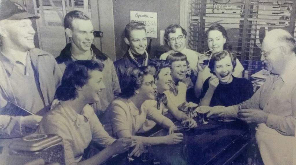 """In this picture from the past, Otis """"Rex"""" Rexroth (right), talks with young customers of his store. Pictured, front row, from left, are Joan Eichelmann, Shirley Korves Novack, Jean Kohler Schutt, Elaine Rehmer Carr and Adele Brandt; back row: Herbie Dubois, Leroy Mechler, Frank Martin, Jean Fridrichs Seigfried and Maggie Hempe. (submitted photo)"""