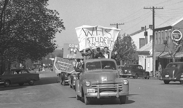 Students parade through town with signs on vehicles protesting the school board's decision not to recognize daylight savings time in 1953. (Bob Voris photo)