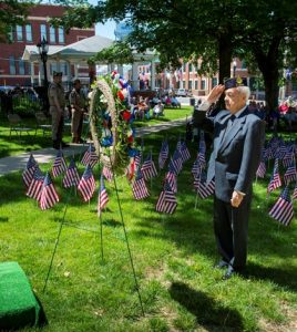 Waterloo American Legion Commander Roy J. May raises his right hand to offer a solemn salute at a ceremonial wreath representing fallen soldiers during Monday's Memorial Day program outside the courthouse.