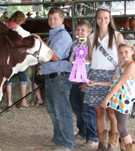 Pictured, from left, Lucas Stumpf receives the trophy for grand champion all breed heifer during judging July 2015 at the Monroe County Fair while his brother Cory proudly stands next to him along with 2015 Monroe County Fair Queen Micki Brinkmann and 2015 Little Miss Monroe County Fair Ellie Day.