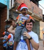 Gutknecht holds up a child on his shoulder during Christmas time in an impoverished area of Salvador. (submitted photo)