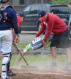 Valmeyer Lakers players served as groundskeepers during the Midsummer Classic at Borsch Park. Pictured, the grounds crew works feverishly to apply diamond dry during Saturday's game between Millstadt and Cape Girardeau. (Corey Saathoff photo)