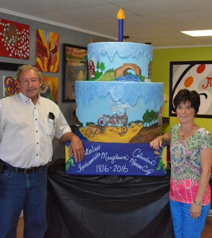 Pictured, from left, are Monroe County Commissioner Delbert Wittenauer and Theresa O'Bryan of Art2Go Studio in Columbia with the second of two ceremonial Bicentennial cakes. (Corey Saathoff photo)
