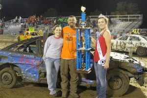 Pictured is Compact Class Figure 8 winner Andy Mercer of Waterloo and passenger Dani Conrad of Columbia with Monroe County Fair Queen Jessica Neary. (Judy Brinkmann photo)