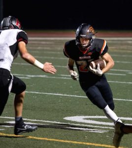 Waterloo's Scott Nanney (right) runs the ball in the second half Friday night against Highland. For more photos from the game, click here. (Alan Dooley photo)