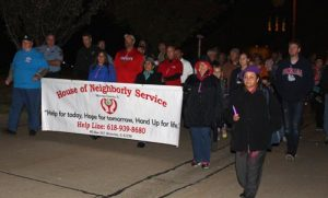 House of Neighborly Service volunteers and supporters march along with law enforcement personnel and others from the community during a Peace Walk held in Valmeyer on Thursday night. (Sean McGowan photo)
