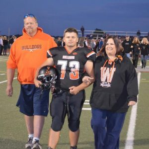 Pictured, WHS senior football player David Woodall escorts his parents onto the field during a pre-game senior night ceremony on Oct. 14. (Corey Saathoff photo)