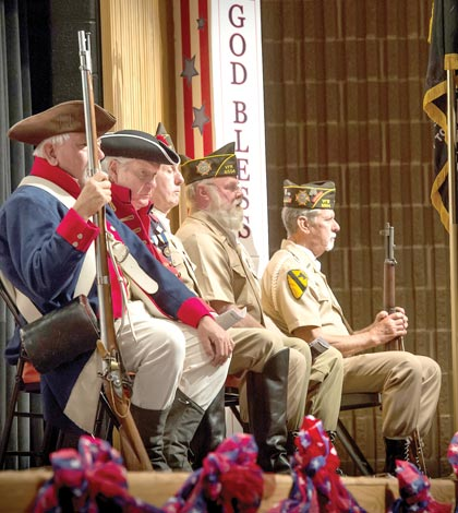 Revolutionary War re-enactors and members of the Waterloo VFW Post 6504 Color Guard listen to guest speaker Col. Laura Lenderman during the Veterans Day program at Waterloo High School on Thursday. (Alan Dooley photo)